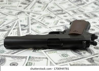 Black gun pistol on stack money 100 dollars background