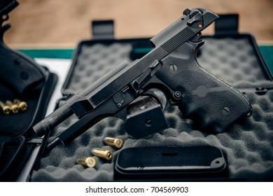 Black guns and boxes at the shooting range.