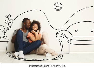 Black guy and his girlfriend imagining their new furnished home against white wall with interior drawings