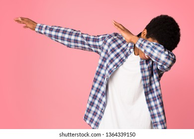 Black guy making dab gesture, having fun on pink studio background