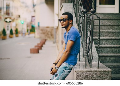 Black guy near stairs in summer city holding a phone