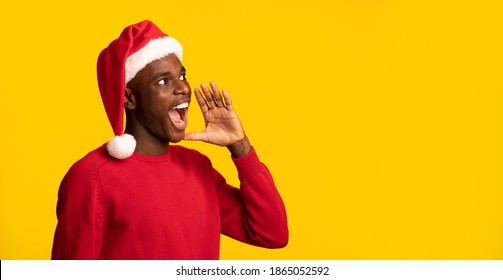 Black Guy In Santa Hat Shouting At Copy Space On Yellow Background, Making Christmas Announcement, Excited African American Man In Red Sweater Informing About Seasonal Sales And Discounts, Panorama
