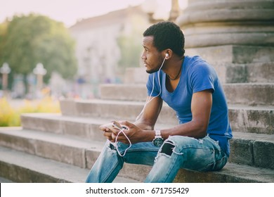 Black guy sitting in summer city on a stairs and holding a phone