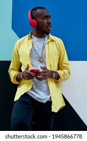 black guy with yellow shirt and red headphones and phone listening to music standing next to a colorful wall