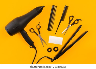 Black hair dryer, comb and scissors on yellow paper background. Top view