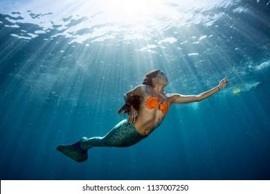black hair Mermaid swimming underwater in the deep blue sea