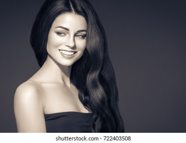 Black hair woman. Beautiful brunette hairstyle fashion portrait with beauty long black hair over dark background black and white