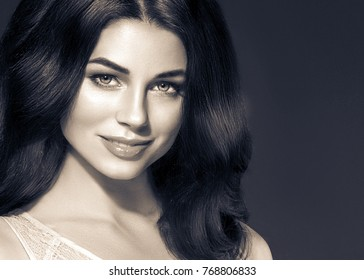 Black hair woman. Beautiful brunette hairstyle fashion portrait with beauty long black hair over dark background black and white. Studio shot.