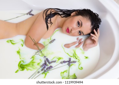 Black hair woman relaxing in a milk bath decorated with green color food paint