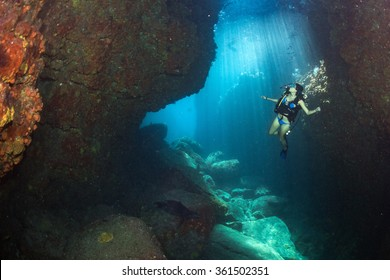 Black hair young and pretty mexican latina Scuba diver in the reef and blue sea cave