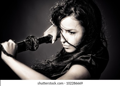 black hair young woman holding katana weapon, studio dark