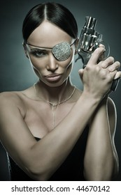 black hair young woman portrait with revolver, studio shot