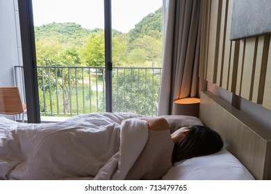 a black hair young woman resting on the bed and watching the beautiful nature view through the window