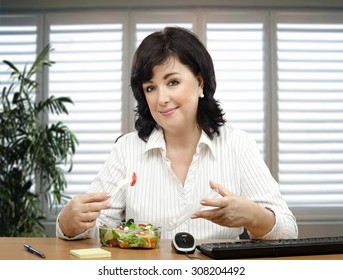 Black haired businesswoman sitting at desk is healthy eating fan. She orders takeaway vegetable salad every lunchtime.