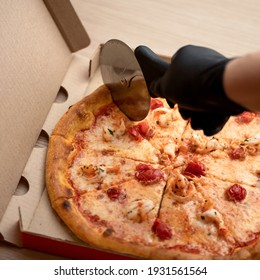 Black hand cuts the pizza with a round pizza cutter. Delicious Pizza. Traditional italian food, top view. Nutrition dinner or lunch. Top view. 1x1 format.
