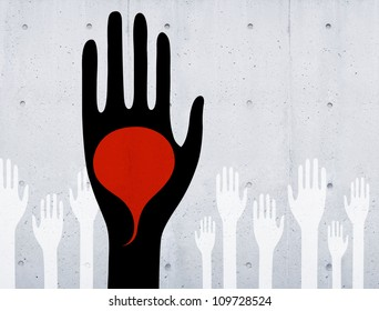 Black hand holding red speech bubble on concrete wall