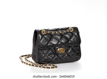 Black handbag with golden chain from genuine leather isolated on white background