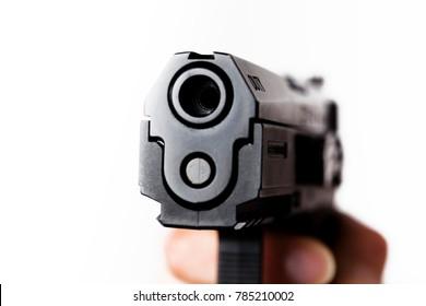 Black handgun being held in human hand on a white background