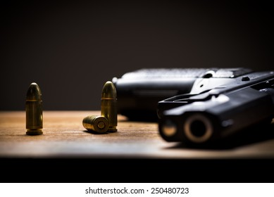 Black Handgun and bullets on a wooden background.