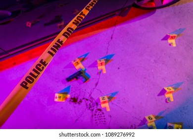 A black handgun lays on the pavement in a crime scene, marked with an evidence marker.