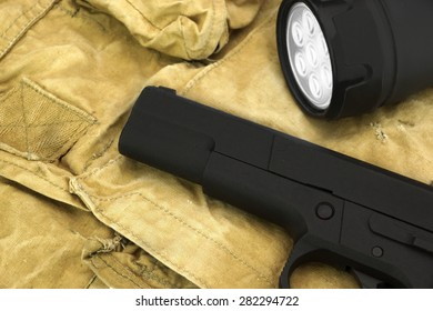 Black Handgun And  Turned On Led Tourch On The  Faded Green Backpack Background Close-up