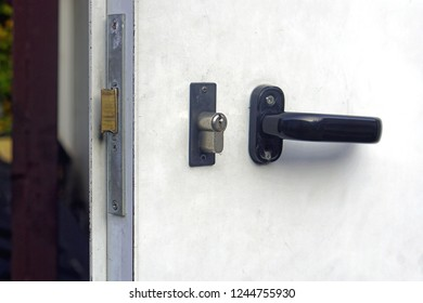 Black handle with lock at metal door