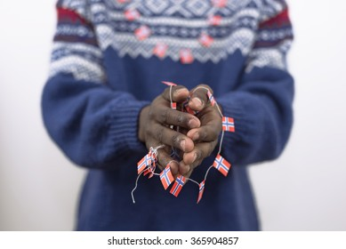black hands holding around small Norwegian flags, dressed in traditional Norwegian sweater. Concept of tolerance, patriotism and ethnic diversity.