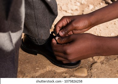 Black hands tieing school shoes on a dirt road.