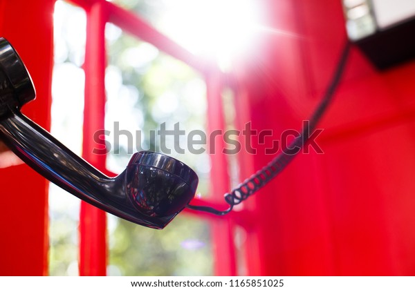 black handset in the red booth. phone handset falls in the red telephone box. The concept of disconnecting a telephone conversation