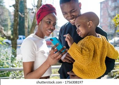 Schwarze glückliche Familie im Freien mit Smartphone-Lächeln - Technologie, Jugendkultur, Familienkonzept