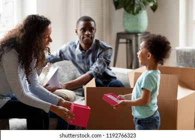Black happy family sitting together in living room with cardboard boxes. African adorable son and laughing mother hold red gift box. Happiness moving relocate at new house, mortgage and loan concept