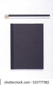 black, hardcover book and pencils in black and white colors, layout on a white desk, close up, top view, vertical