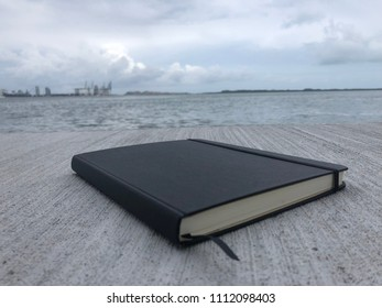 Black hardcover journal in a scenic writing spot