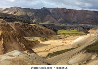 Black hardened lava and colorful rhyolite mountains  in the central highlands, Landmannalaugar, Iceland