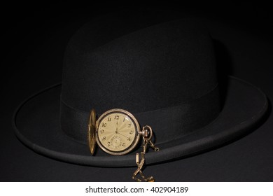 Black hat with a pocket watch on a black background