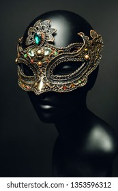 Black head of mannequin in creative metal mask with jewels