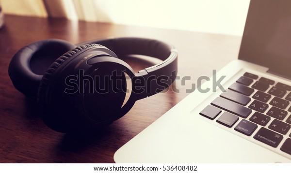 Black headphone and laptop computer on wooden background. Vintage filter.