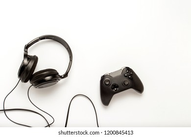 Black headphones and a gamepad on a white isolated background. Concept of the game on the console or computer. Rest after work. Cybersport. Flat lay, top view