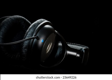 black headphones on black background, copy space for the text
