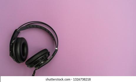 Black headphones on pink background. Top view
