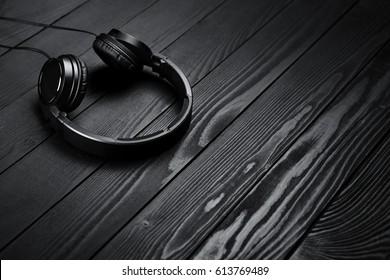 Black headphones on black wooden dark background