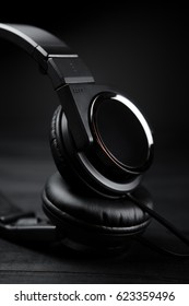 Black headphones on black wooden dark background