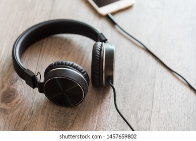 Black headphones and smartphone on wooden background.