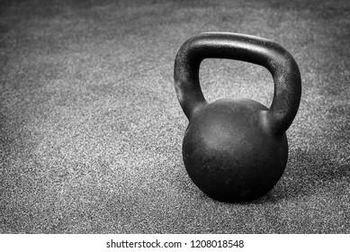 Black heavy kettlebell on gray floor, background