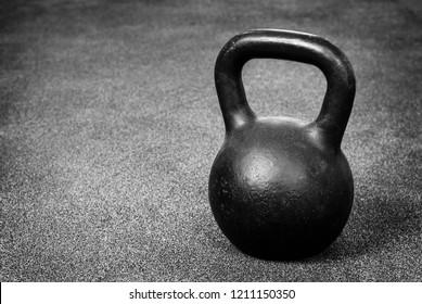 Black heavy kettlebell on gray floor, weightlifting