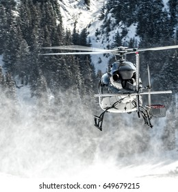 Black helicopter departed from a snowed altiport with whites reflection in the fuselage. The rotor's power raises the snow creating a dust. It transport skiers and material above the mountains.