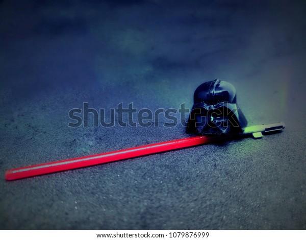 A black helmet with the light saber sword on the black background