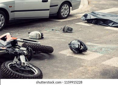 Black helmet and motorcycle on the road after fatal collision with a car