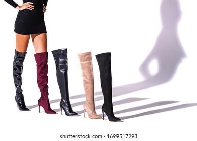 black hessian boots on the legs of the model on a white background with shadows and other hessian shoes. boots are higher than a knee. studio shot. thin legs. fashionable boots.