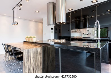 Black high-gloss open kitchen in modern style